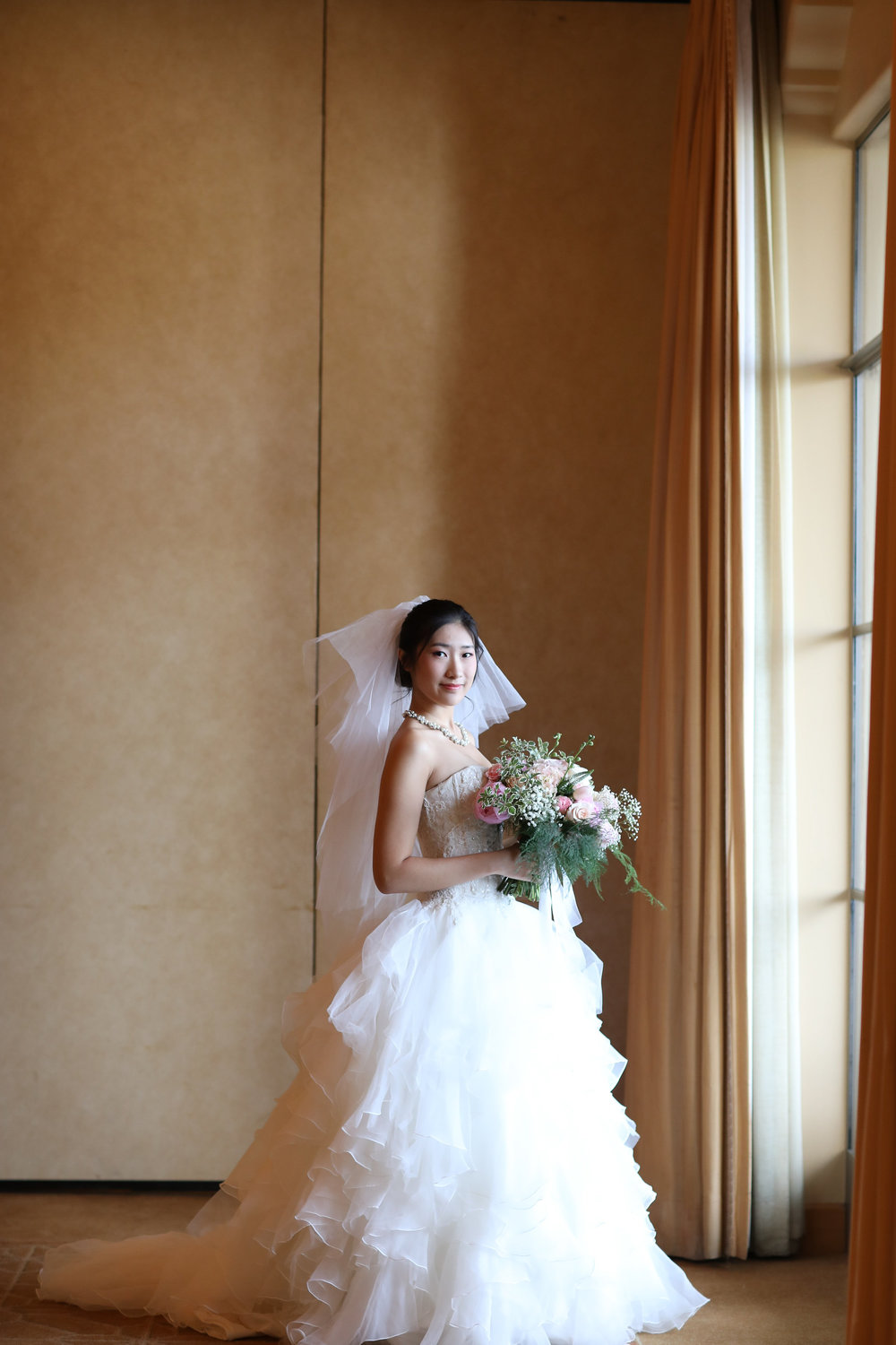 Beautiful Chinese bride at the Resort at Pelican Hill wearing a ruffled teared designer wedding dress.