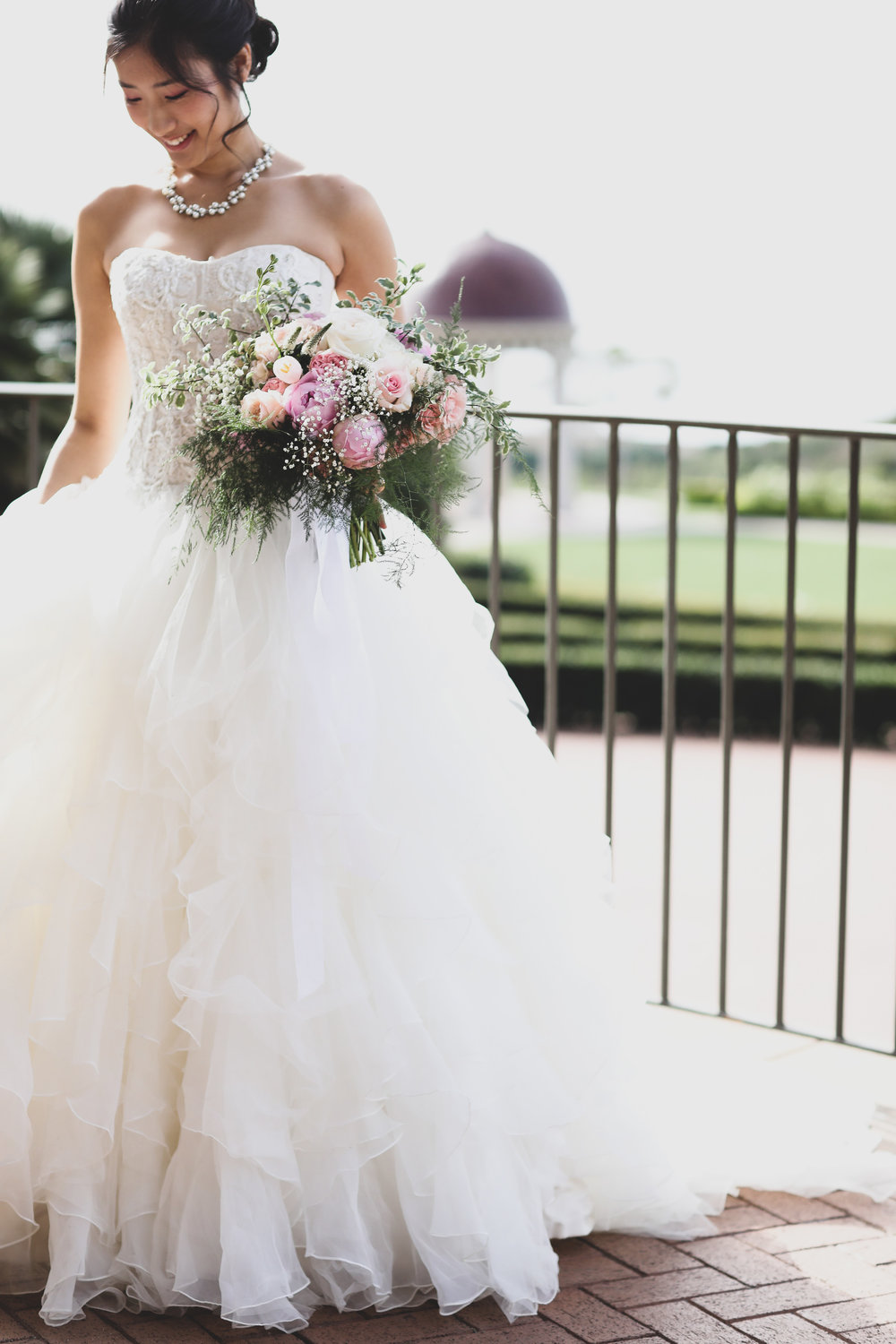 Beautiful Chinese Bride at the Resort at Pelican Hill in Orange County wearing a ruffled designer dress with a pink rose bouquet done by Bleudog Floral.