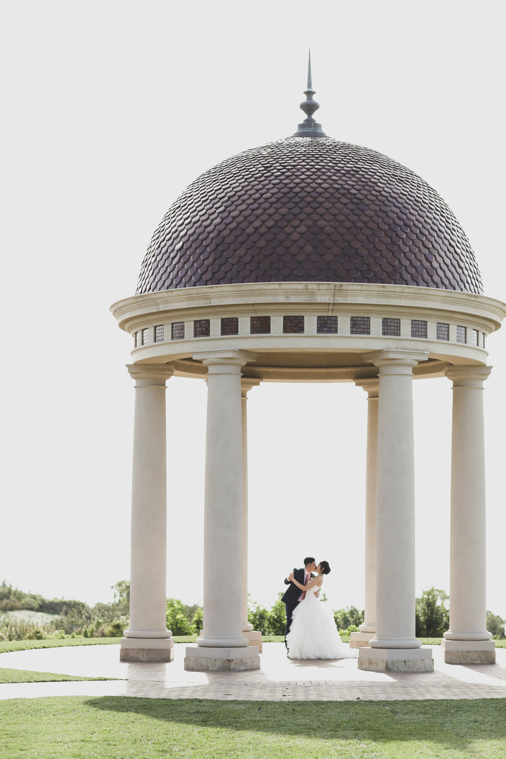 World famous rotunda at the beautiful Orange County wedding venue, the Resort at Pelican hill. Bride and groom kissing.