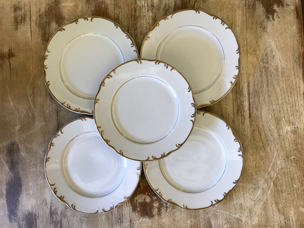 Assorted mismatched gold china bread plates.