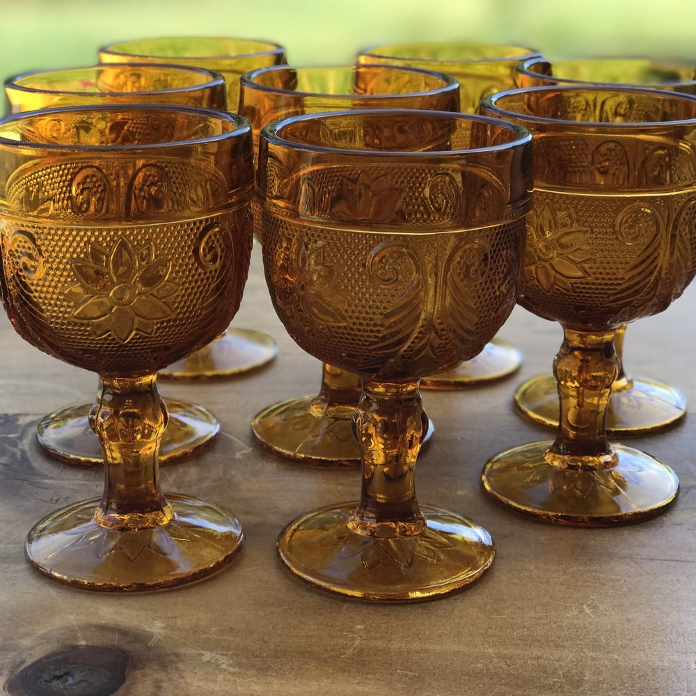 Assortment of amber drinking glasses. All mismatched style but the same amber color. Vintage Boho look.. Wedding rentals in Temecula Valley.