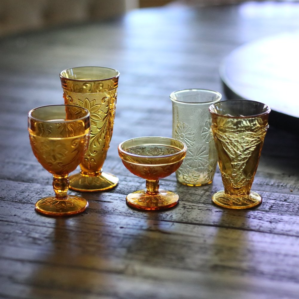 A variety of amber colored glass drinking glasses. Vintage and mismatched but they all look great together. Wedding table rentals.
