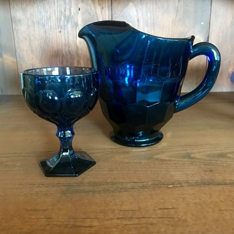 Dark blue glass pitcher with a Fostoria goblet. Vintage rentals in Murrieta.