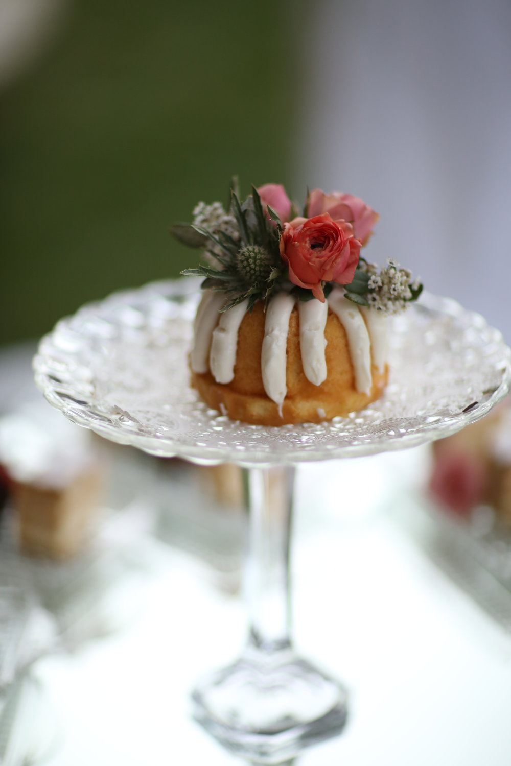 Nothing Bundt Cake on a tall cut glass pedestal platter. Decorated with flowers. Wedding reception.