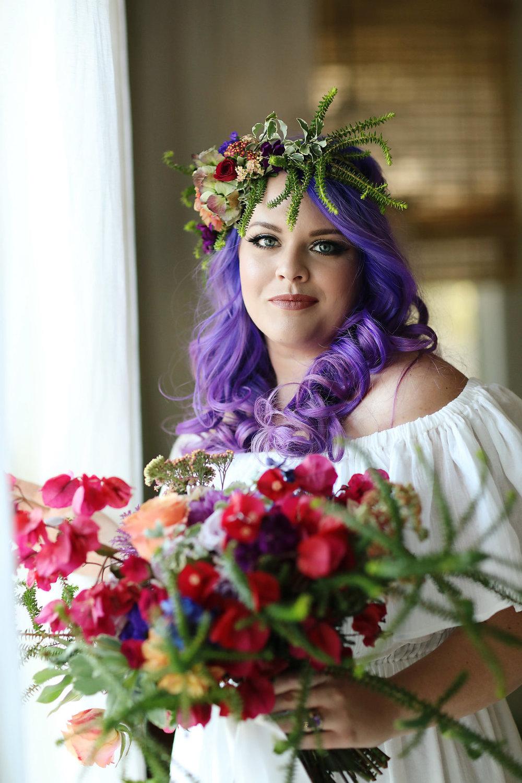 Bright colored floral arrangements in a bridal bouquet enhances the brides ultra violet hair.