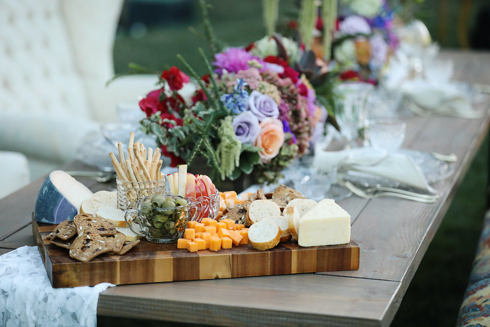 Custom charcuterie board on top of our industrial farm table set for the wedding party. Rentals from Birdie in a Barn vintage rentals in Murrieta.