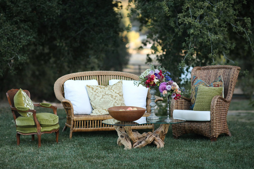 Bohemian seating area at a wedding reception in Murrieta, California. Rattan chairs and a grapevine table with a glass kidney shaped top.