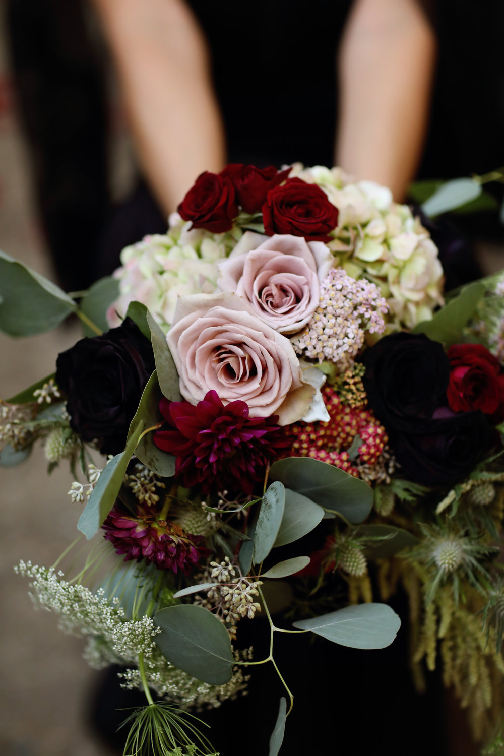 Brides bouquet Sith black dahlias, thistle, roses, and seeded eucalyptus