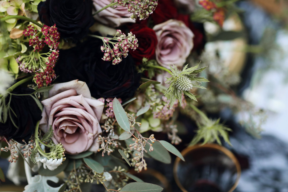 Floral bridal bouquet and centerpieces including a black dahlia.