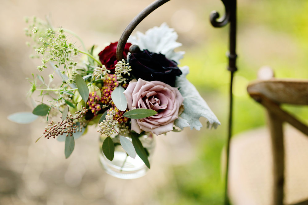 Delicate floral arrangements hanging from Shepard hooks in the wedding ceremony.