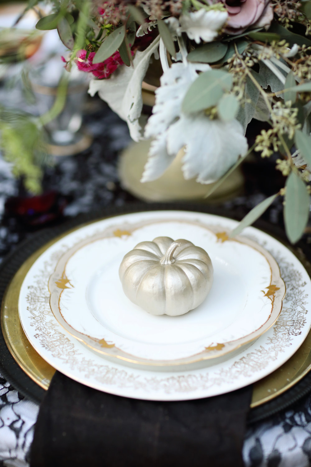 Gold china, gold chargers, black napkins, gold pumpkins, wedding table.
