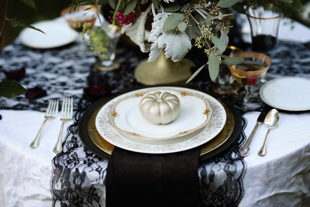Formal wedding table setting. Gold china, gold chargers, vintage silverware, black lace, gold rimmed goblets. All vintage rentals from Birdie in a Barn.