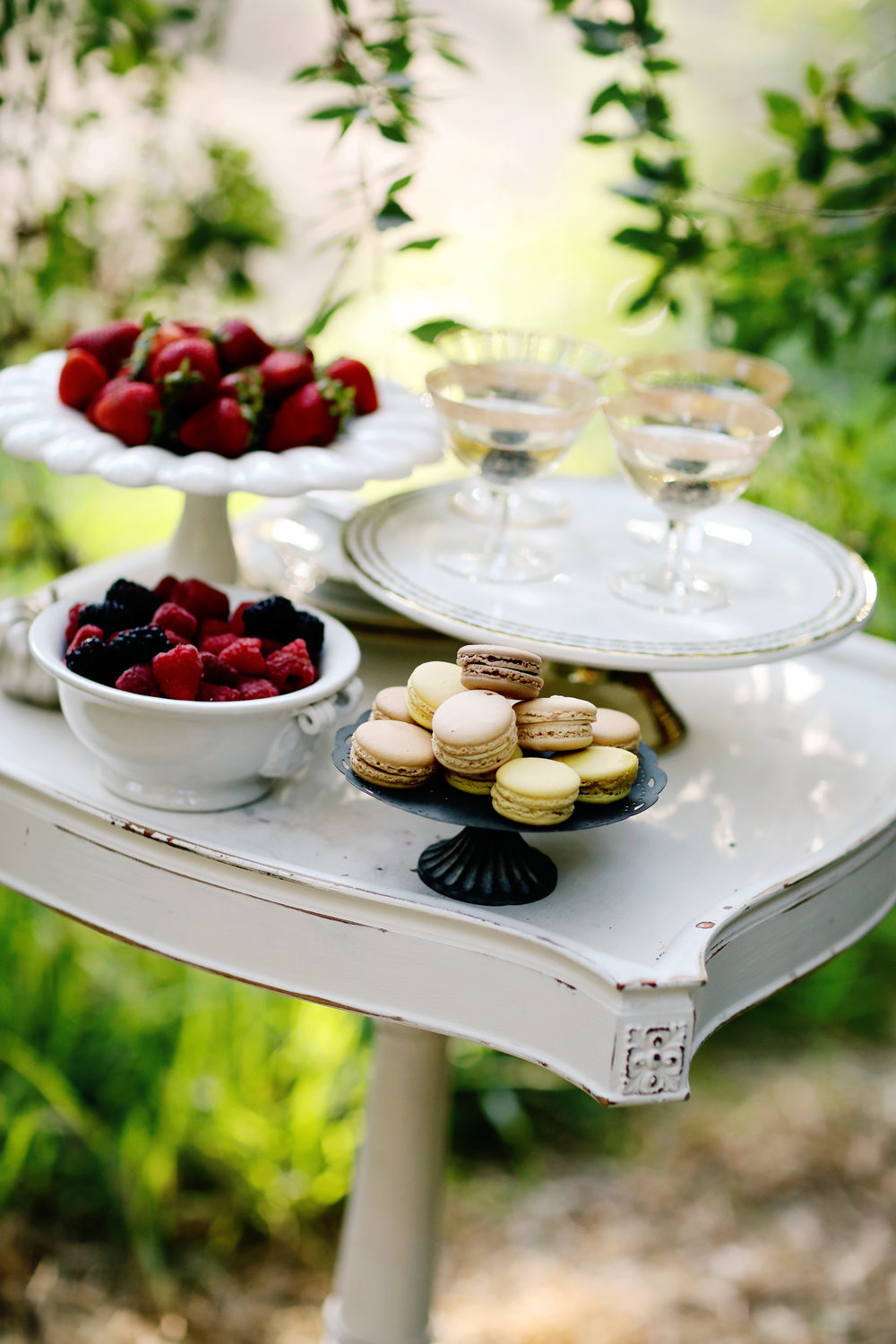 Vintage antique white wooden side table with desserts on the top for a wedding. Macaroons on milk glass pedestals.