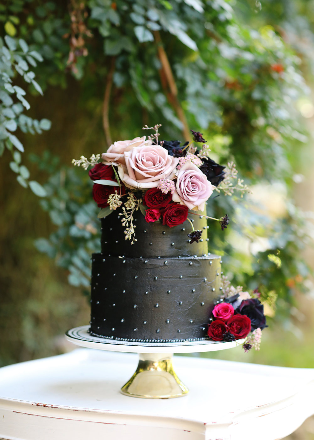 Black wedding cake decorated with flowers on a gold pedestal cake plate.