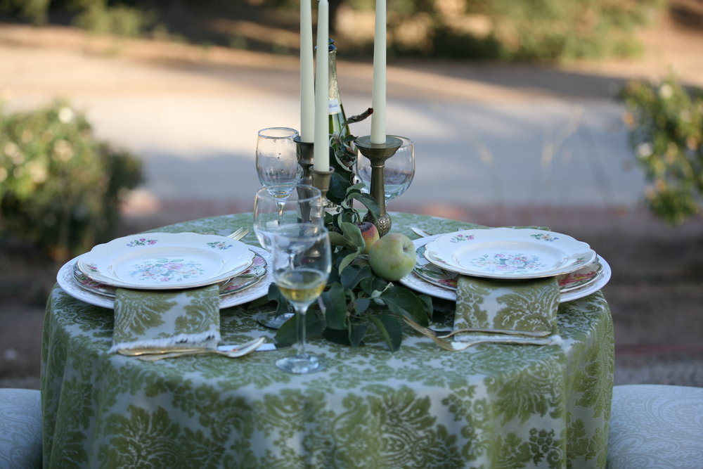 Sweetheart table at a wedding set with a charger plate and decorative china plates.