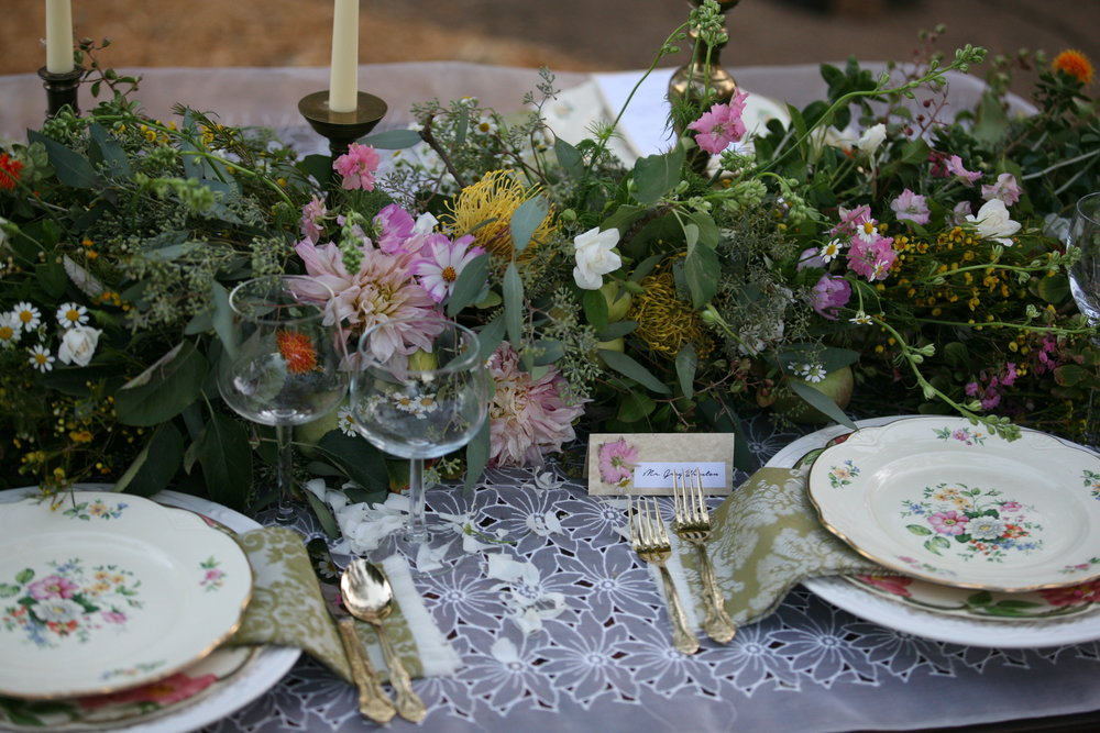 Formal wedding table set with charger plate, china, silverware, and floral centerpiece.