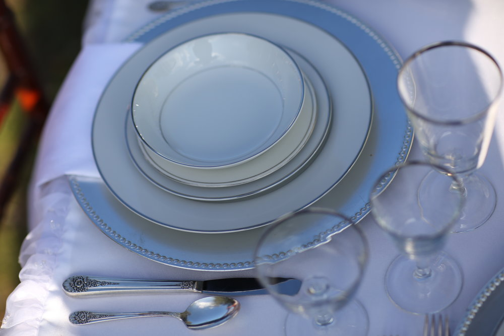 Silver china on top of a silver charger with silverware and silver rimmed crystal goblets. Vintage rental for weddings.