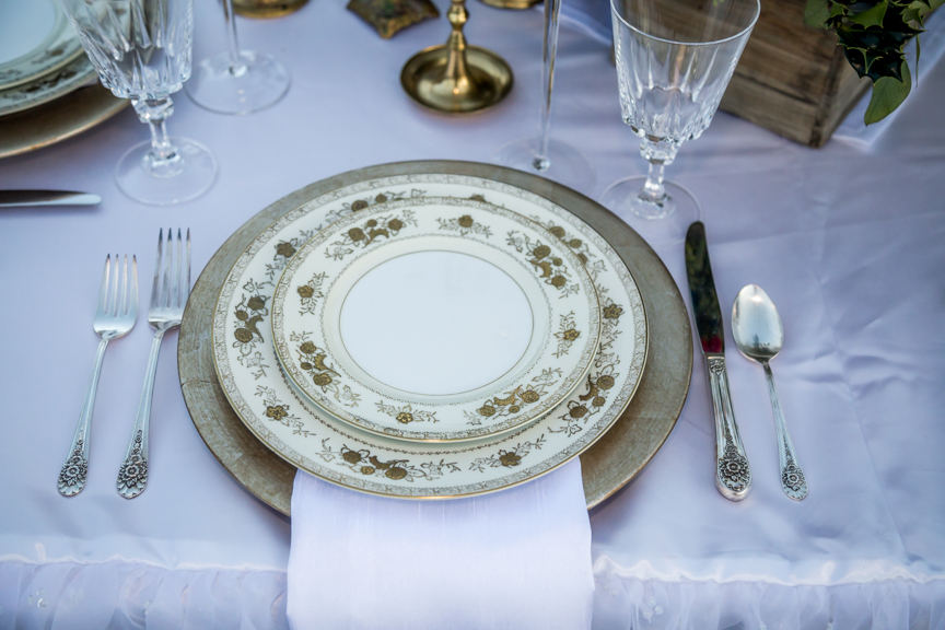 Gold charger plate with vintage gold china set for a wedding table.