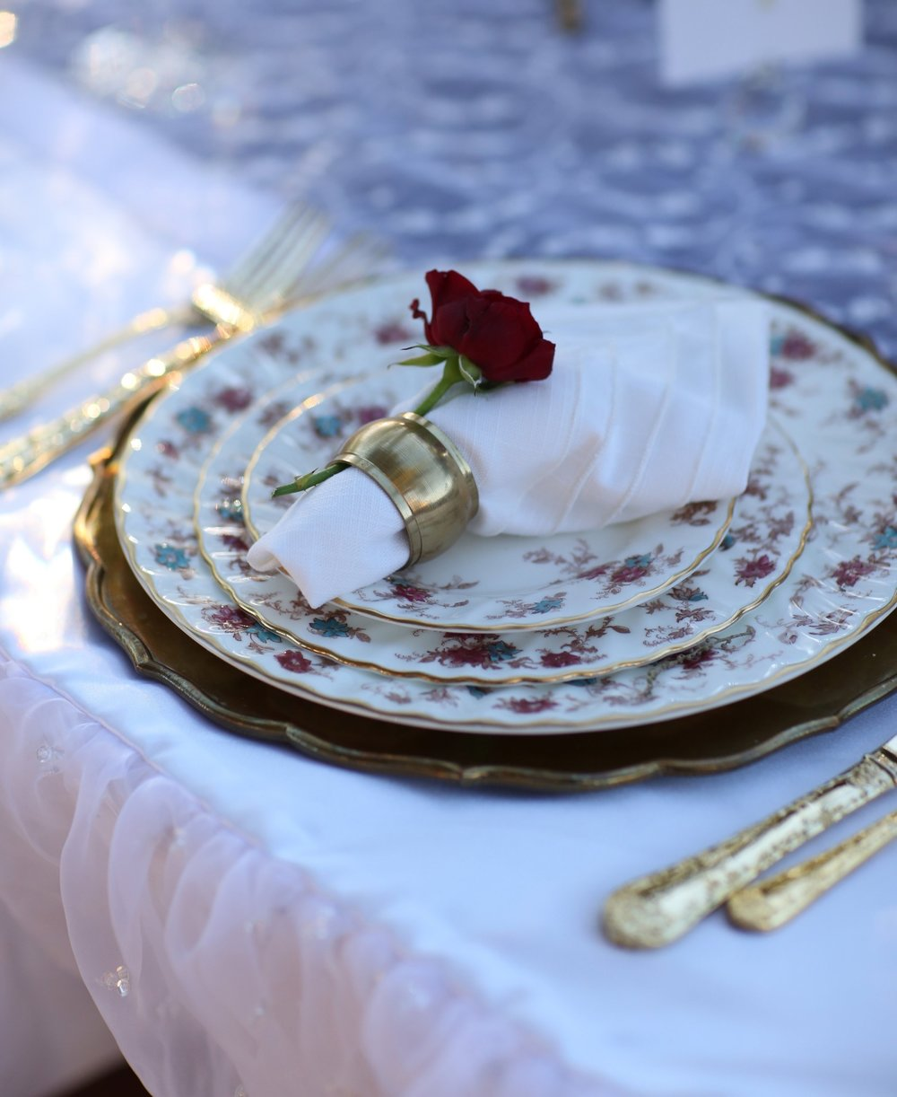 Beautiful table setting of vintage china, silverware, and brass charger plate. Wedding table.