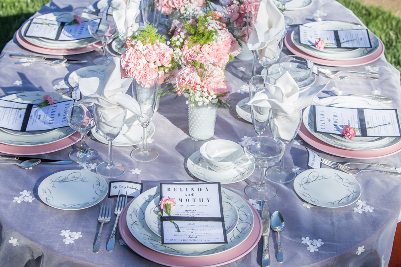 Pink charger plates set at a wedding table with mid century modern china.