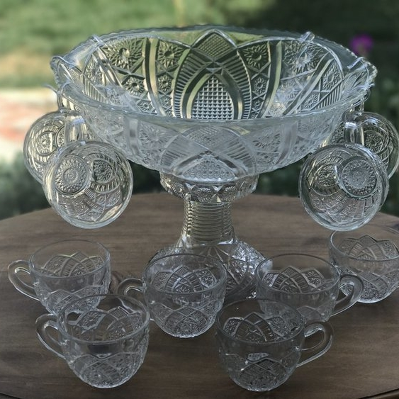 Small Punch Bowl Set   Cut glass punch bowl with an intricate swirl pattern on decorative base. Comes with 10 matching cups. Measures 7.5 inches tall with the base included.