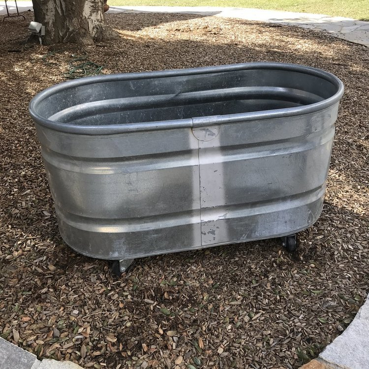 "Galvanized Beverage Trough   Heavy duty galvanized metal trough tub on two wheels. 50"" long x 26"" wide x 26"" tall."