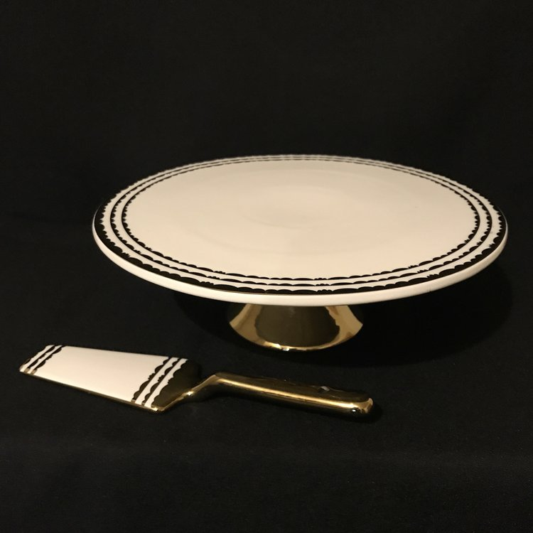 White and Gold China Cake Plate   White china cake stand on gold metallic pedestal. Top of the plate has gold metallic concentric circle pattern around the edge. Comes with gold metallic cake server.