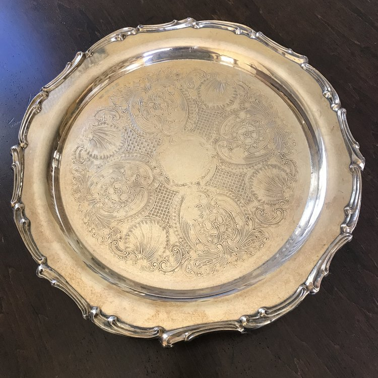 "Silver Cake Pedestal Plate   Silver plated cake stand with scalloped edge on a pedestal. 4"" tall x 14"" round. Intricately decorated top. May use polished or Shabby Chic."