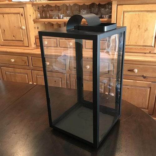 "Large Black Lantern   Matte black metal lantern with glass sides. Openable door on one side. Handle can be used for hanging. 20"" tall x 10"" square. Comes with three candles in glass."