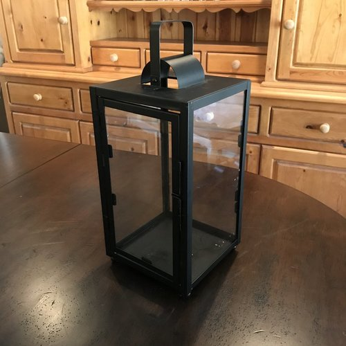 "Medium Black Lantern   Matte black metal lantern with glass sides. Openable door on one side. Handle can be used for hanging. 16"" tall x 8"" square. Comes with three candles in glass,"