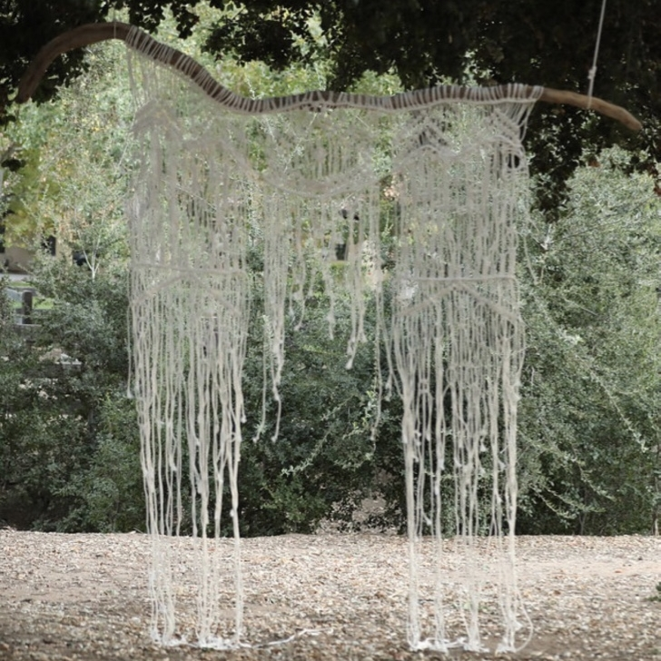 Abigale   This Boho beauty is a one of a kind piece. It is a 6' macrame backdrop on a 9' piece of driftwood straight out of the Colorado River. It looks amazing as in a ceremony setting.
