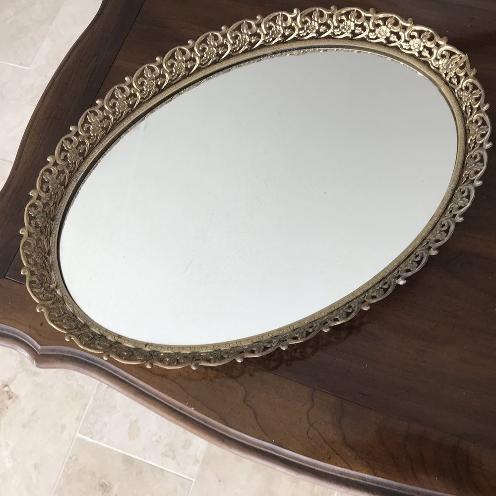 "Oval Brass Dresser Mirror   Mid-century Modern, Hollywood Regency, oval mirrored tray with floral gold trim. Oval 16.5"" long x 12"" wide."