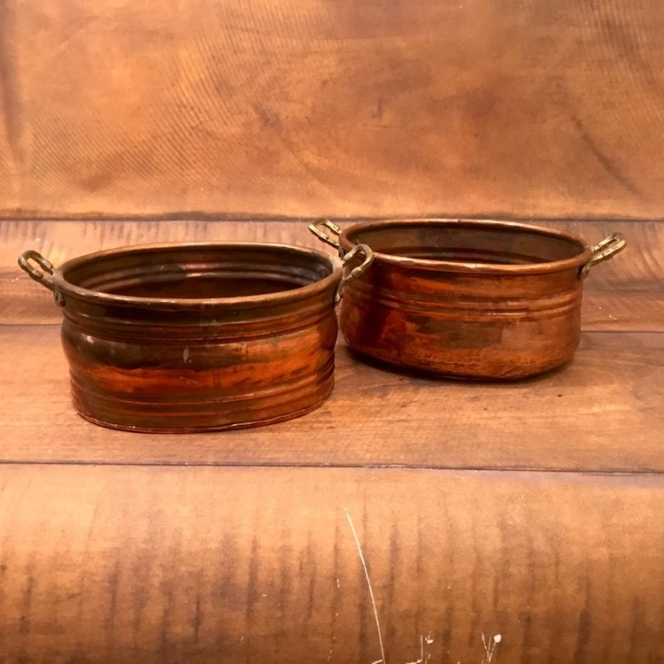 Little oval copper pots with handles.