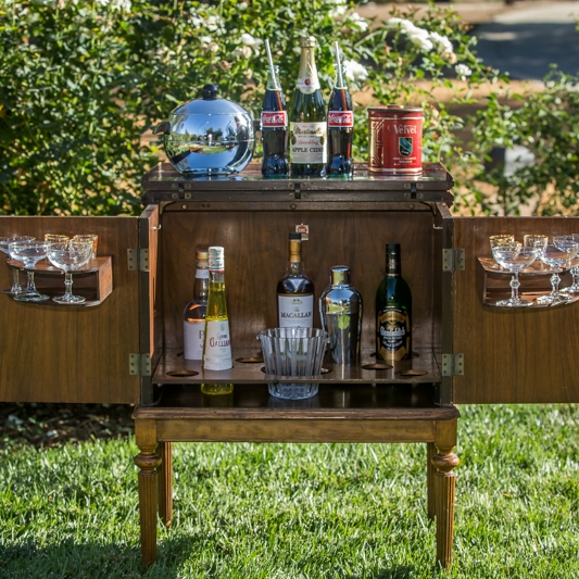 "Tanner   A true Mid-century Modern portable mini bar on wheels. Chrome lid that opens for mixing drinks. Doors open for ice bucket, bottles, and glasses. 27"" long x 17"" wide. 33.5"" high."