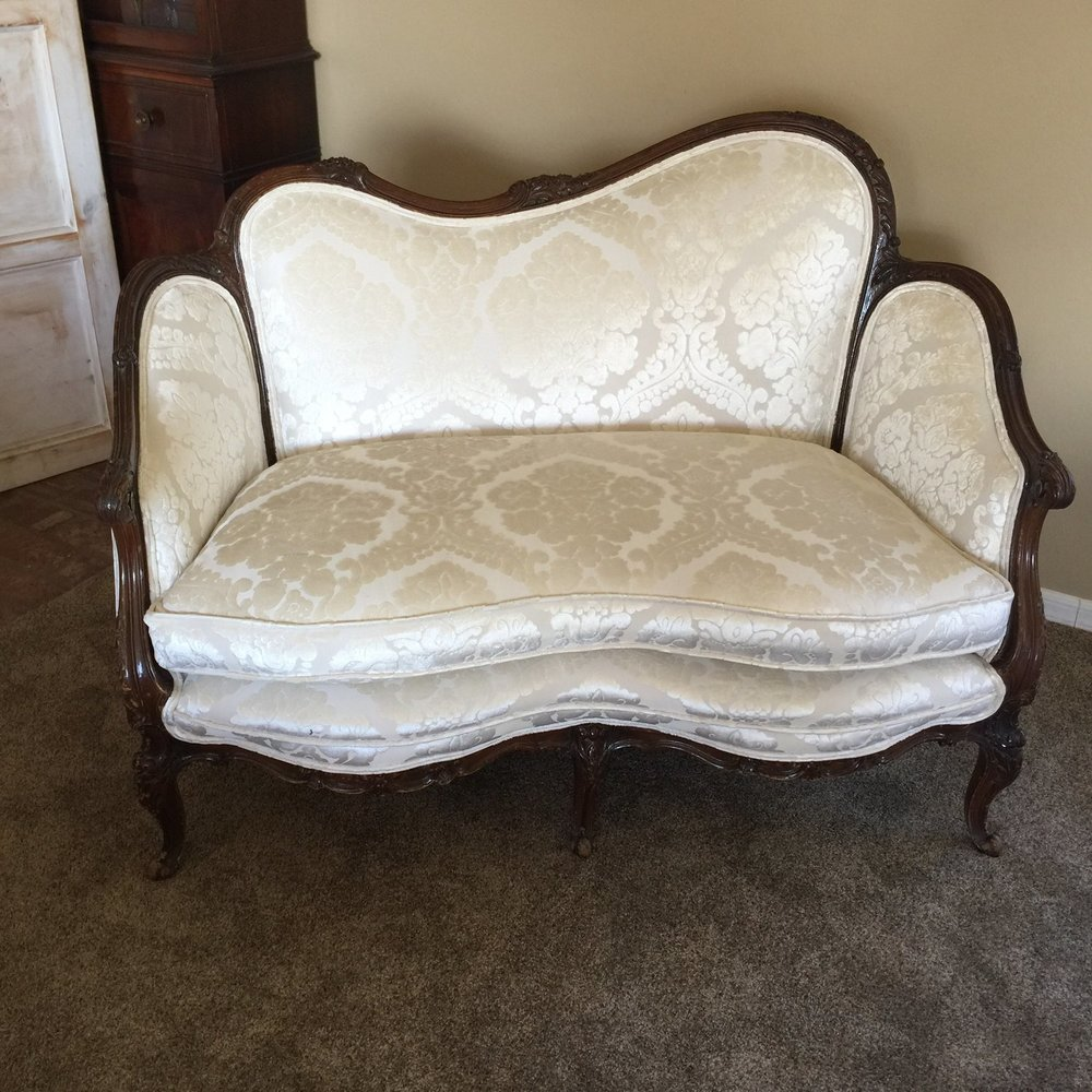 "Carole   Vintage settee with a floral carved wood frame. Off set curved back with a scalloped front seat. Double piped. Off white velvet damask. So cozy for the wedding couple. 50"" long x 29"" wide x 36"" tall"