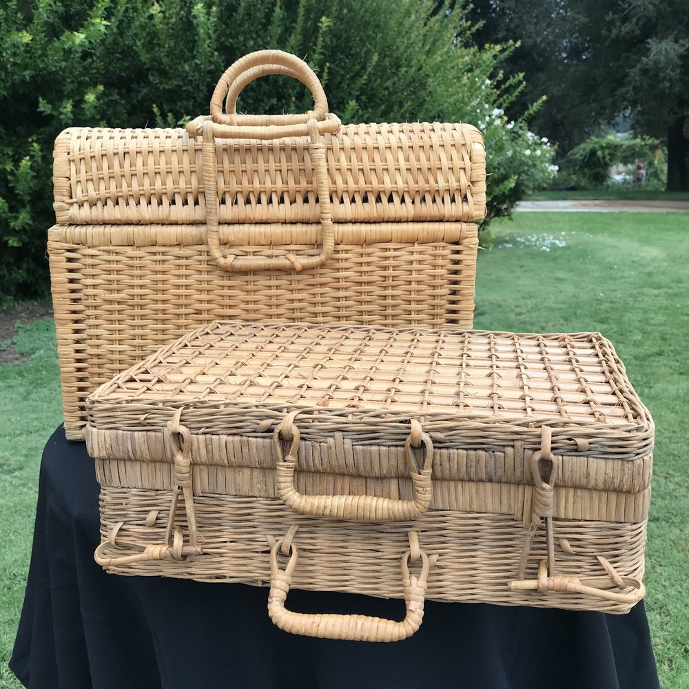 Vintage assorted wicker picnic baskets and suitcases.