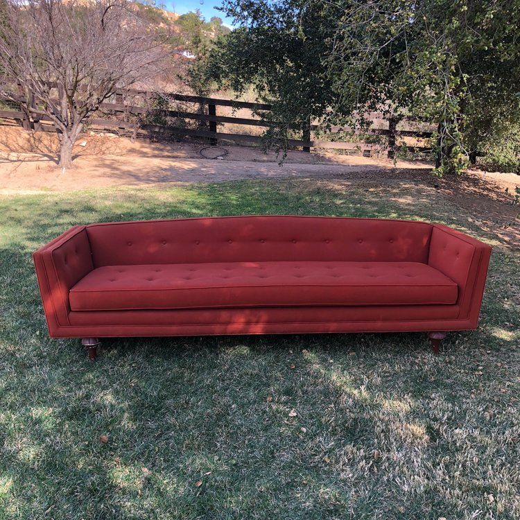 "Winona   Original vintage Mid-century modern couch. Pulled straight from a house that time forgot. Tufted, single pillow seat, straight legs, rad orange color. Low profile back and arms. This couch will be a conversation piece at your wedding. 96"" Long x 30"" wide x 26"" high."