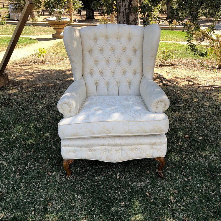 """The Gabor Sisters  Cream on cream floral print wingback chair with tufted back and wooden legs. Pairs with Pearl. 37"""" high x 29"""" wide x 21"""" deep."""