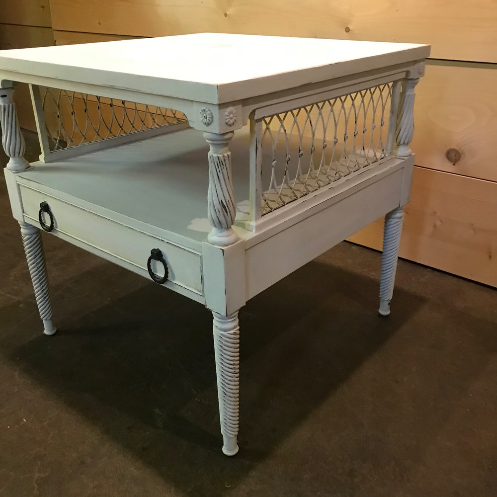 Two tiered chalk painted white side table with metal side inserts. Vintage rentals.