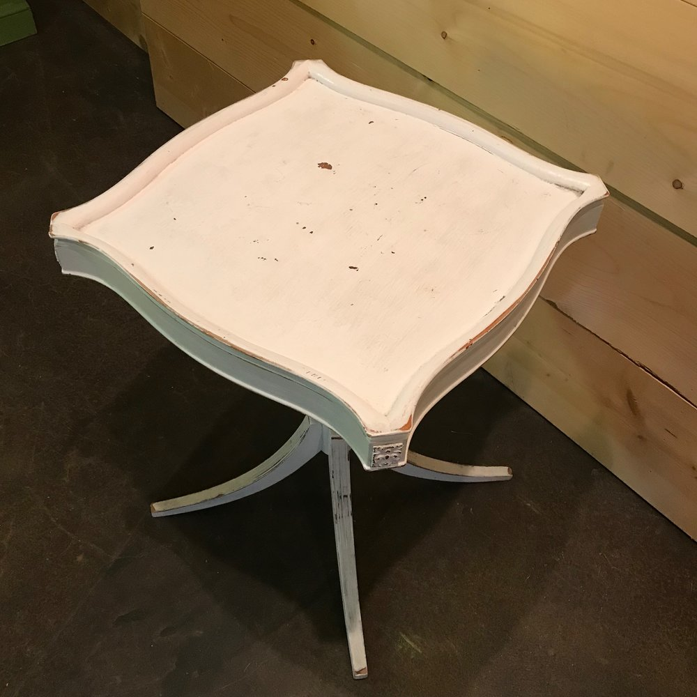 White wooden side table with flared legs and scalloped top. Vintage rentals.
