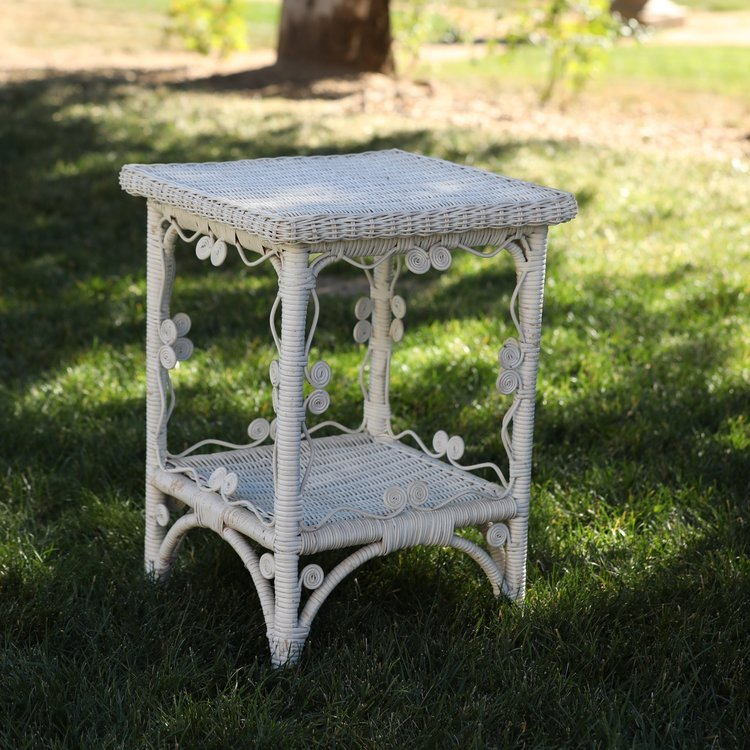 "Melinda   White wicker accent table. 18"" square by 24"" tall. Table top and bottom shelf. Decorative white scrolls around the table top and bottom."