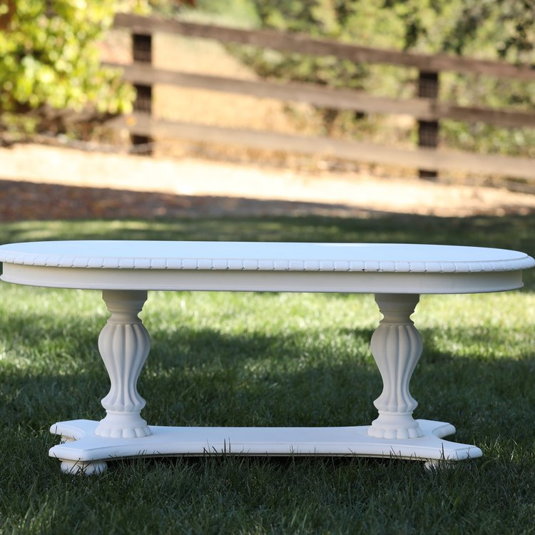 """Riley   Wooden, white coffee table with sculpted base and legs. It really is darn cute! 48""""x24.5"""" oval by 21"""" high."""
