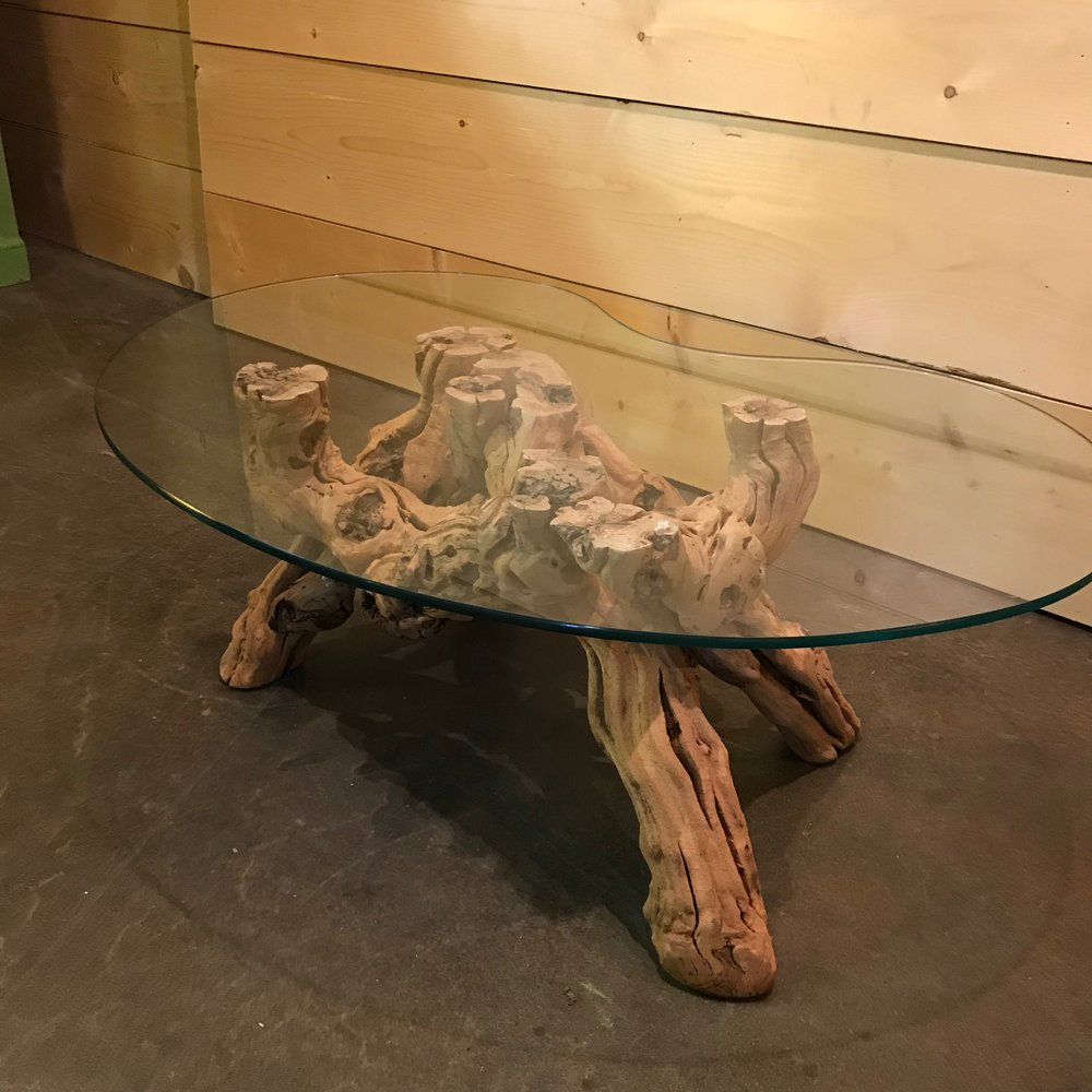 """Marlo   Smaller version of Brutus. Grapevine table with a kidney shaped glass top. 15"""" high x 42"""" long x 25"""" wide."""