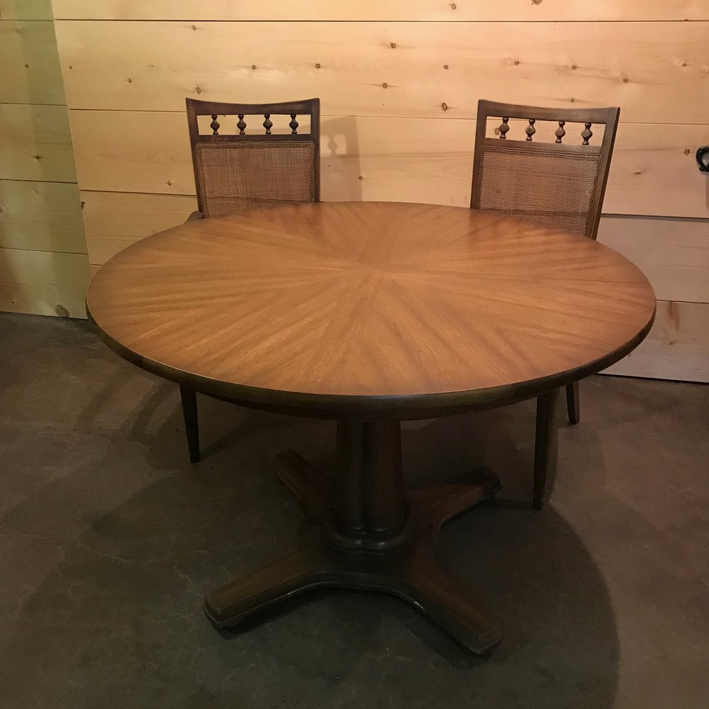 Mid-century Modern dining table with two cane back chairs.