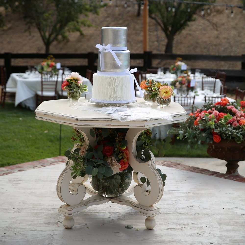 Hexagon white shabby chic table with wedding cake on it and floral below. Vintage furniture rentals