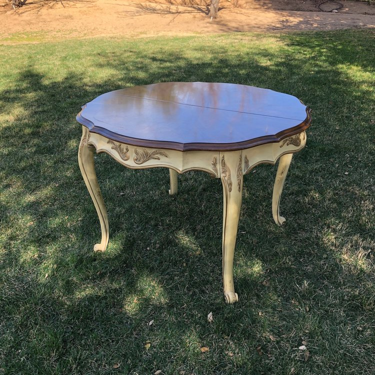 "Phyllis   Dark Walnut French Provincial table with a cream base and hints of gold leafing. Has two leafs available with apron attached. Leaf 20"" wide. Table without leafs 42"" long x 38.5"" wide x 29.5"" high. Perfect for a sweetheart table."