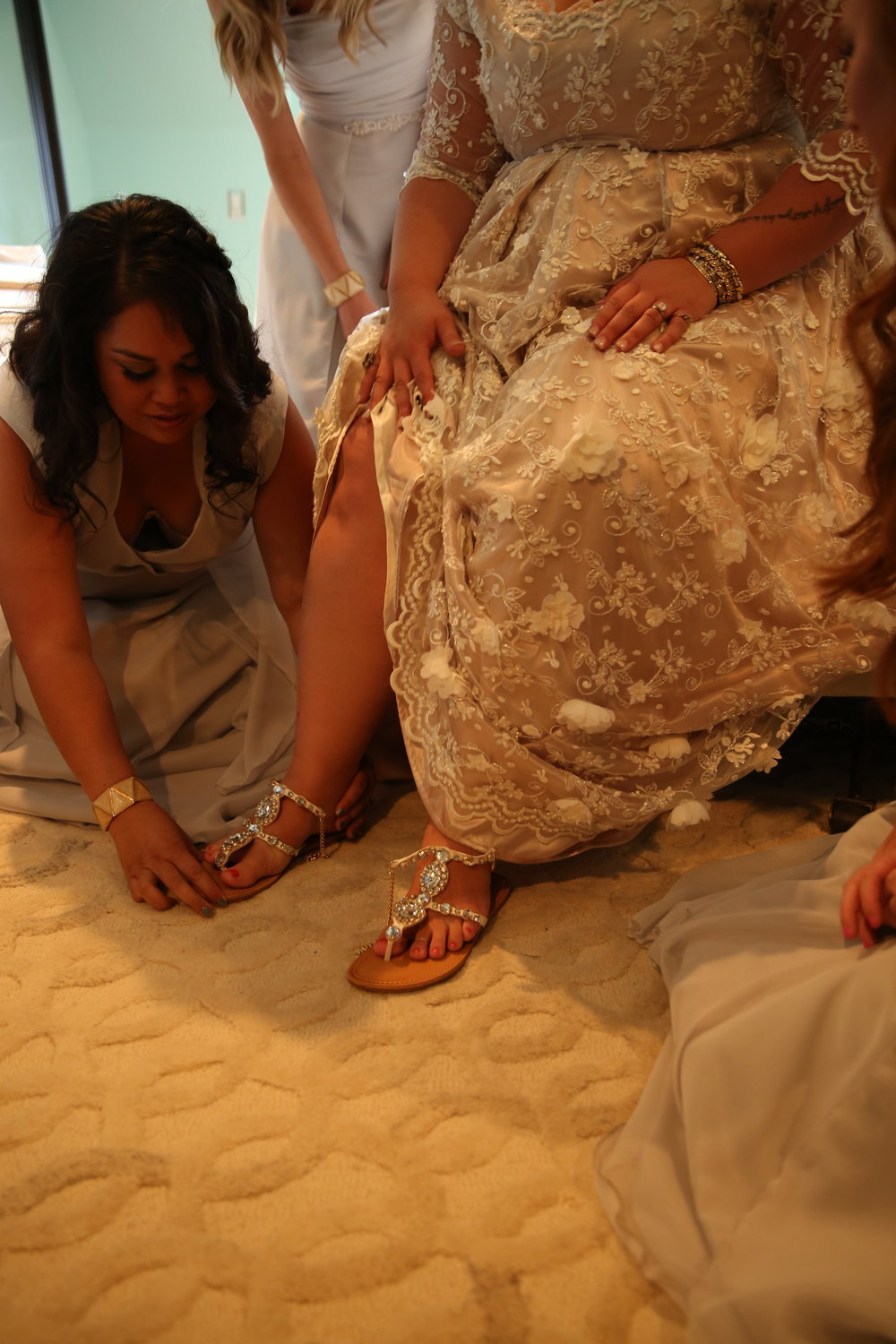 The brides bridesmaids helping her put on her wedding shoes for her big wedding day in Murrieta California.