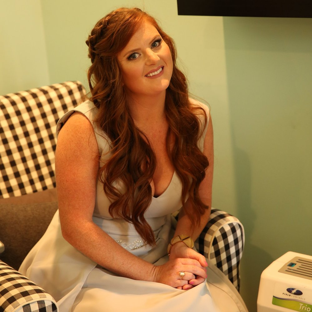 Bridesmaid with red hair wearing a grey dress sitting on a black and white checkered chair. Wedding rentals by Birdie in a Barn.