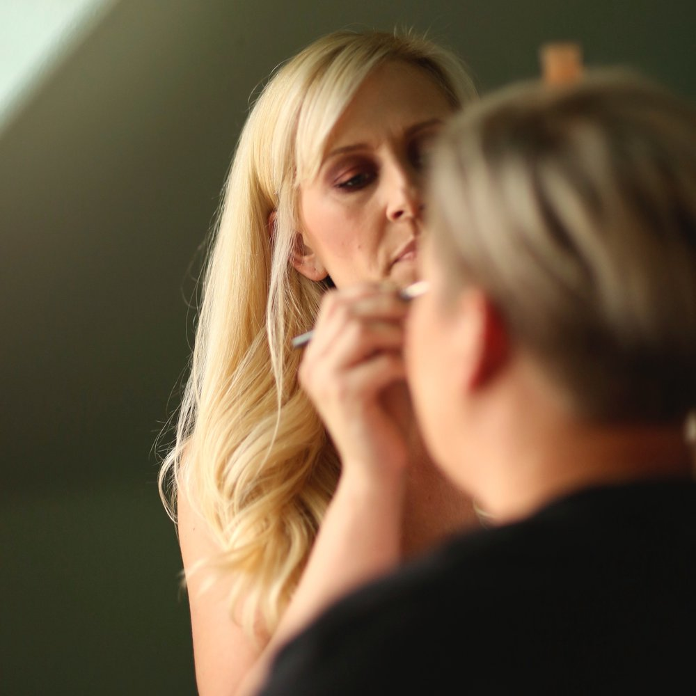 Young bride getting made up by a professional make up artist in the bridal suite of the venue.