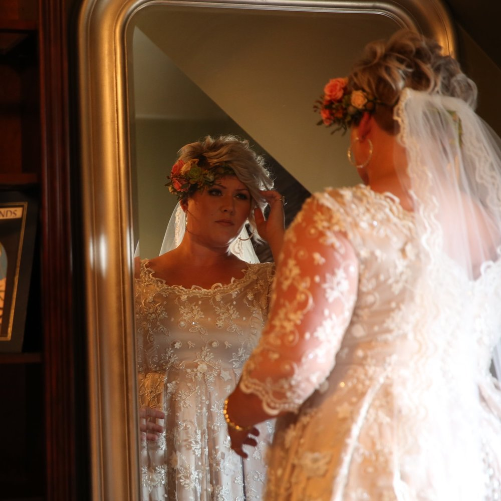 Bride looking at her reflection in the mirror as she contemplates her walk down the aisle to her groom.